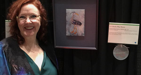 """Christina Fairley Erickson with her 3rd place entry """"Cheeky Blue Heron"""" at the International Quilt and Fiber Art Exhibition 2019"""